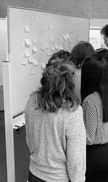 crowd at a whiteboard using post-it notes during a workshop